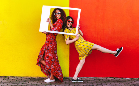 Two women friends with blank photo frame standing against colored wall outdoors. Female travelers posing at camera with empty picture frame.