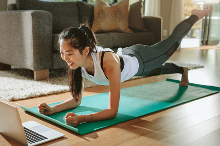 Foto de Smiling woman exercising at home and watching training videos on laptop. Chinese female doing planks with a leg outstretched and looking at laptop. - Imagen libre de derechos