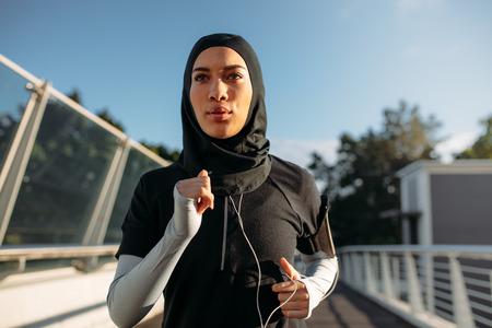 Foto de Healthy sporty woman wearing hijab jogging outdoors in the city. Islamic woman running early in the morning. - Imagen libre de derechos