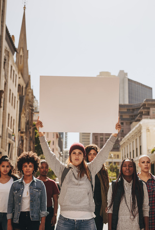 Photo pour Multiracial group of females protesting outdoors on road. Female with group holding blank banner during a protest. - image libre de droit