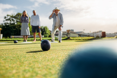 Old man in hat throws a boules standing in position in a lawn with his friends standing behind in background. Group of senior people playing boules in a park.