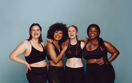 Foto de Portrait of group of women posing together in sportswear against a gray background. Multiracial females with different size standing together looking at camera and smiling. - Imagen libre de derechos