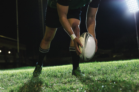 Photo pour Rugby player dropping the ball to the ground for kicking as it touches the ground. - image libre de droit