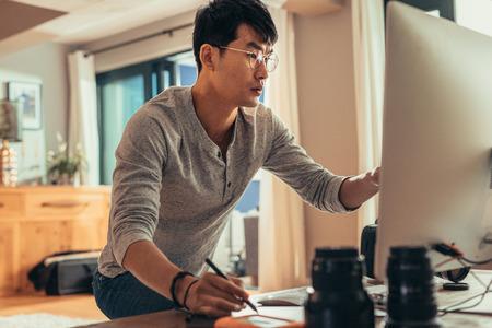 Foto de Photographer editing sample shoots on his computer in studio. Man working on computer in photo studio. - Imagen libre de derechos