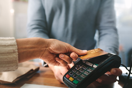 Photo for Pharmacist accepting credit card by contactless payment.  Woman purchasing products in the pharmacy. Pharmacist hands charging with credit card reader. - Royalty Free Image