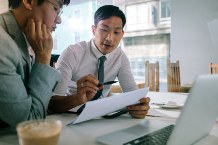 Foto de Young asian businessman explaining a document to his manager sitting at cafe table. Business professionals discussing over some paperwork at coffee shop. - Imagen libre de derechos