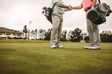 Photo for Two senior men shaking hands and when meeting on a golf course. Senior golfers at the golf course greeting each other with a handshake. - Royalty Free Image