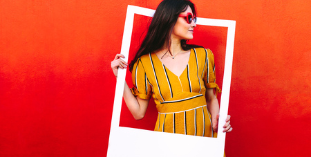 Foto de Beautiful female model standing against a red wall with photo frame. Pretty woman looking away through a empty picture frame. - Imagen libre de derechos
