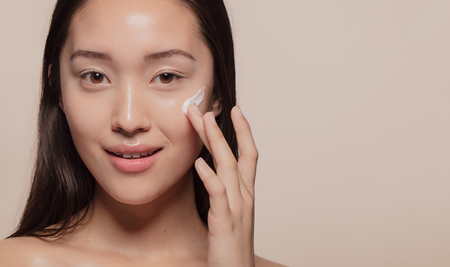 Foto de Close up of a asian woman applying moisturizer to her pretty face. Female model putting cream on her glowing face skin. - Imagen libre de derechos