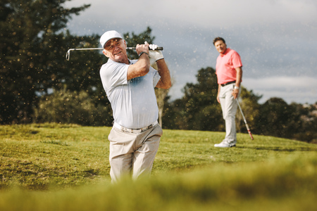 Foto de Pro golfer playing on the course with second player standing at back looking on. Man hitting the ball out of a sand bunker during the game. - Imagen libre de derechos