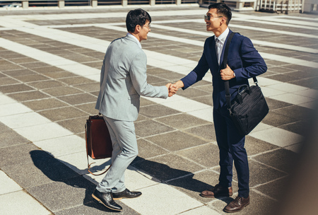 Photo for Two asian businessmen shaking hands outdoors in the city. Business people greeting each other outdoors. - Royalty Free Image
