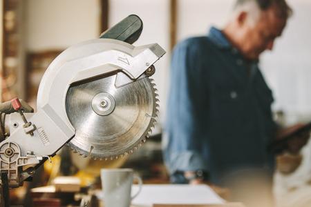 Foto de Circular wood saw in carpentry workshop with carpenter in background. Cutting tool in carpentry workshop. - Imagen libre de derechos