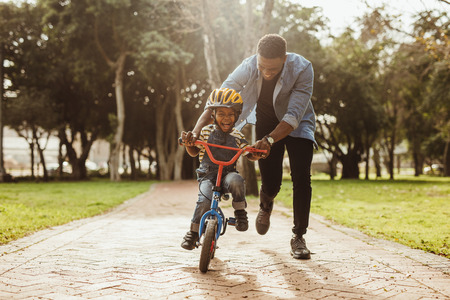 Foto de Boy learning to ride a bicycle with his father in park. Father teaching his son cycling at park. - Imagen libre de derechos
