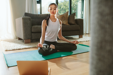Photo for Fit woman doing yoga exercise while watching tutorial on laptop at home. Attractive chinese woman exercising on a mat and watching instructional videos on laptop. - Royalty Free Image