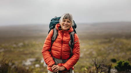 Foto de Portrait of a smiling female hiker standing on top of a hill on a winter day. Senior woman wearing jacket and backpack hiking on a hill. - Imagen libre de derechos