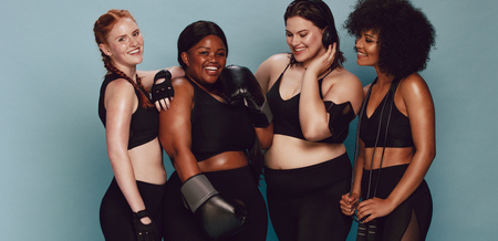 Photo pour Group of women of different race and body size in sportswear standing together. Diverse women with sports equipment looking at camera against grey background. - image libre de droit
