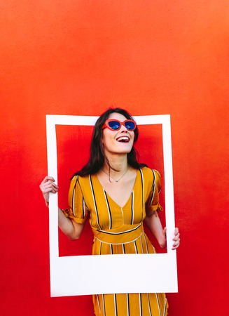 Photo pour Stylish woman standing against the red wall and holding a large photo frame. Beautiful girl wearing sunglasses looking through blank picture frame. - image libre de droit