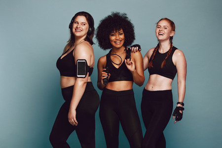 Foto de Portrait of mixed race women standing together against grey background and laughing. Diverse group women in sportswear. - Imagen libre de derechos