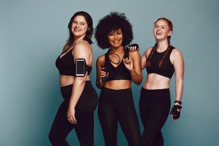 Foto de Portrait of mixed race women standing together against grey background and laughing. Diverse group women in sportswear. - Imagen libre de derechos