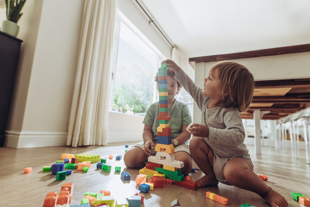 Foto de Kids making a tower using building blocks. Happy kids playing with toys sitting on floor at home. - Imagen libre de derechos