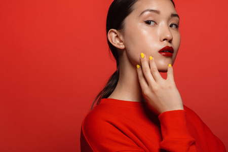 Foto de Portrait of attractive young asian woman with beautiful make up on red background. Asian female model with red top and lipstick. - Imagen libre de derechos