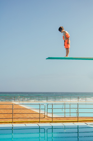 Photo pour Boy with sleeve floats standing on high spring board and looking at swimming pool below. Boy learning to dive from diving platform at outdoor swimming pool. - image libre de droit