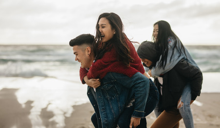 Photo pour Young men carrying female friends on their back along the sea. Group of friends piggybacking outdoors on the seashore. - image libre de droit
