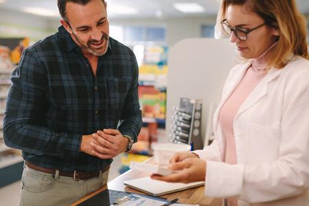 Female pharmacist holding medicine box giving advice to customer in chemist shop. Pharmacist suggesting medical drug to buyer in pharmacy drugstore.
