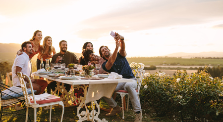 Photo pour Group of friends taking selfie on a smart phone at dinner party. Young people on dinner party in garden taking selfie. - image libre de droit