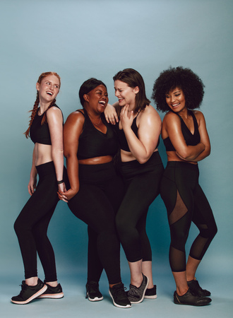 Photo for Group of female standing together in sportswear over gray background. Multi-ethnic woman with different size smiling together. - Royalty Free Image