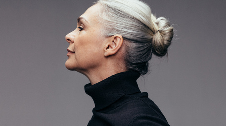Photo pour Side view of senior woman on gray background. Profile view of mature woman in black casuals. - image libre de droit