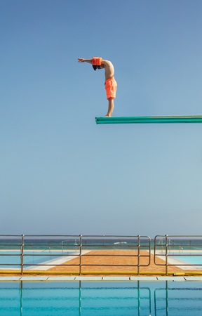 Photo pour Boy stands on a diving platform about to dive into the swimming pool. Boy standing on high diving spring board preparing to dive. - image libre de droit