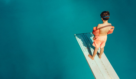 Photo pour Top view of boy standing on spring board learning to dive during swimming class on a summer day. Boy learning swimming at outdoor pool. - image libre de droit