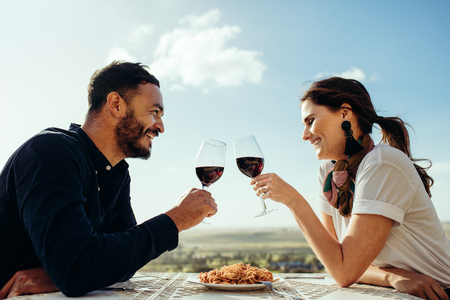 Foto de Side view of a couple sitting in an open air restaurant drinking red wine. Smiling couple toasting wine sitting at a restaurant. - Imagen libre de derechos