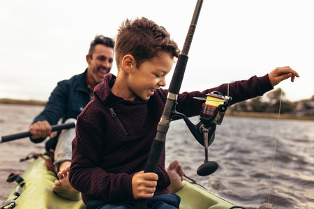 Foto de Kid fishing in lake with his father. Kid releasing the thread tied to the fishing rod in the lake to catch fish. - Imagen libre de derechos