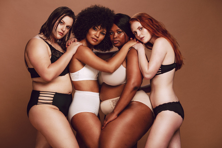 Group of different size women in lingerie hugging each other and looking at camera. Diverse group of women in different underwear together on brown background.
