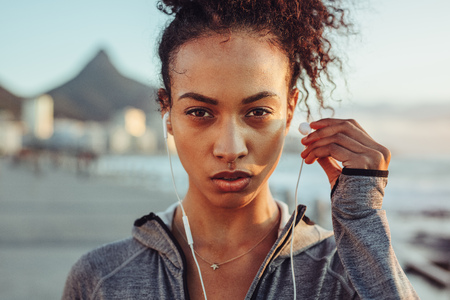 Foto de Close up of woman athlete wearing earphones outdoors. Female listening to music during workout. - Imagen libre de derechos