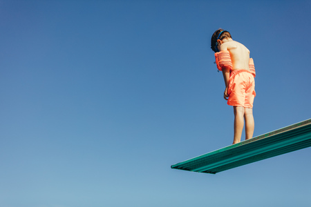 Photo pour Low angle shot of boy with sleeves floats on diving board preparing for dive in the pool. Boy standing on diving spring board against sky. - image libre de droit