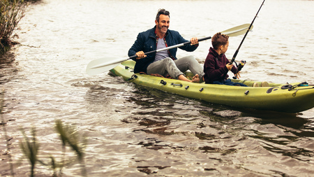 Foto de Father and son out for fishing in a lake in a kayak. Kid looking for fishes in the lake holding a fishing rod while his father rows the boat. - Imagen libre de derechos