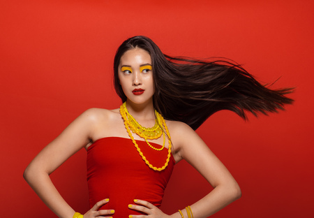 Photo for Attractive woman with stylish stage make up and hair flying on red background. Asian female model with creative make up and accessories. - Royalty Free Image