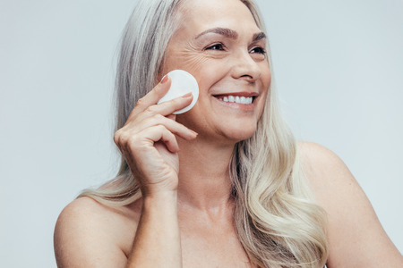 Photo pour Smiling old woman cleansing her face with a cotton pad against grey background. Happy female cleaning her face skin with a cotton pad. - image libre de droit