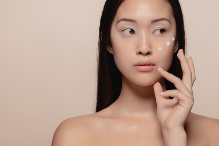 Photo for Close up of a beautiful young woman applying moisturizer to her face. Asian female model putting cosmetic cream on her face and looking away. - Royalty Free Image