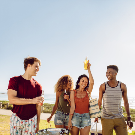 Photo pour Group of men and women at walking outdoors with beers. Friends having a great time together. Young people going on picnic on a summer day. - image libre de droit