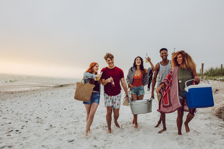 Foto de Group of young people walking on the beach carrying a cooler box and beverage tub. Young men and woman on sea shore. - Imagen libre de derechos