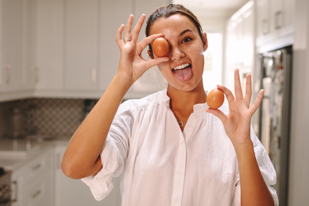 Photo pour Funny woman with brown eggs sticking out her tongue in kitchen. Pastry chef having fun in the kitchen. - image libre de droit