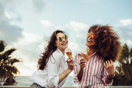 Foto de Two female friends enjoying ice cream together on a summer day. Cheerful young women eating icecream at seaside promenade. - Imagen libre de derechos