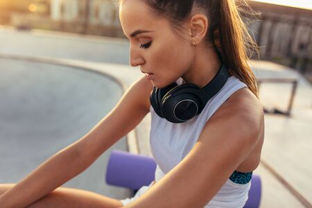 Photo pour Fitness female sitting with headphones around her neck after exercising. Woman resting after workout outdoors. - image libre de droit