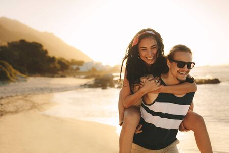 Photo pour Young man and woman on vacation on a beautiful summer's day. Happy man carrying a woman on his back walking on beach. - image libre de droit