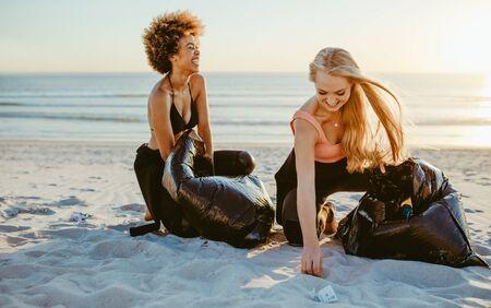 Photo pour Happy female surfers doing trash tag challenge on beach. Women cleaning up beach area. - image libre de droit