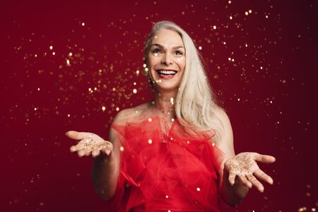 Photo pour Excited senior woman throwing glitters in studio. Caucasian senior woman playing with golden star glitters over red background. - image libre de droit
